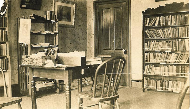 Black and white photo of the library. There are a couple book cases and a desk with a chair.