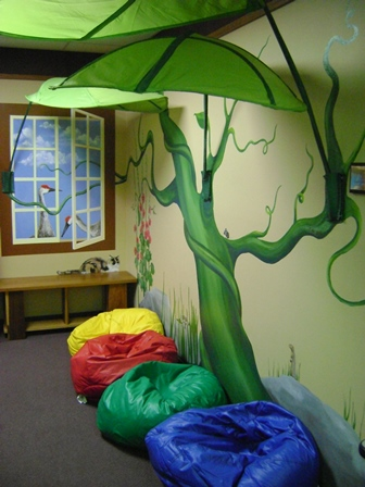 reading nook with bean bags and leaves, mural of window, bean stalk and animals