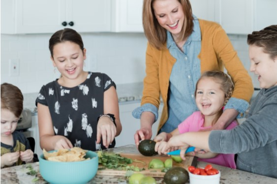 Parent in kitchen with childre preparing food