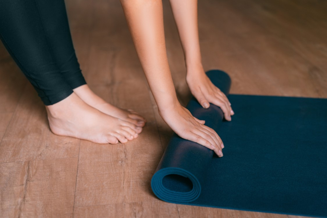 person spreading a yoga mat on the floor