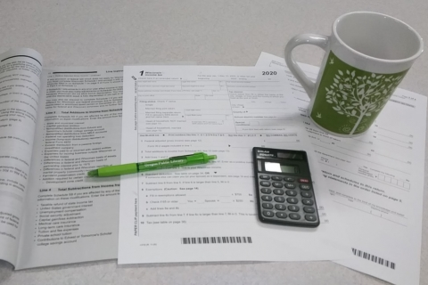2020 Tax forms shown with pen, calculator, and coffee mug
