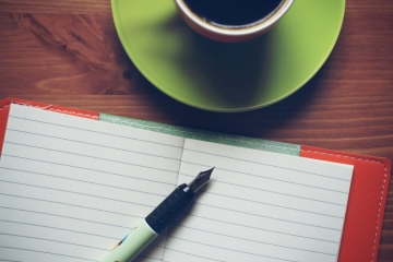 coffee, open notebook, and pen